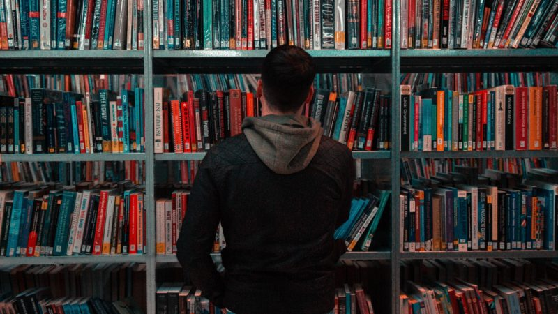 person wearing black and gray jacket in front of bookshelf